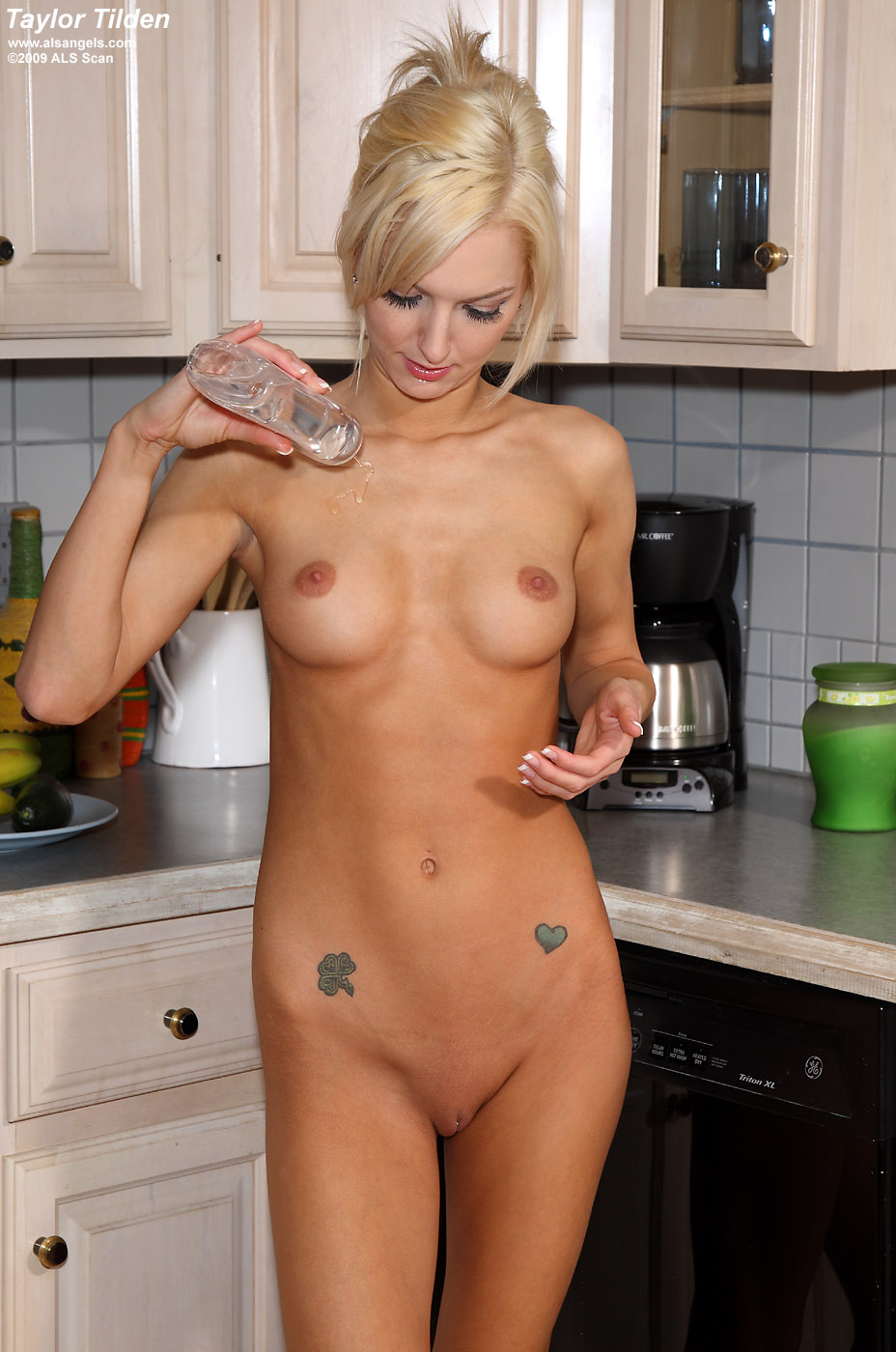 Smiling Nadia Taylor Strips In The Kitchen